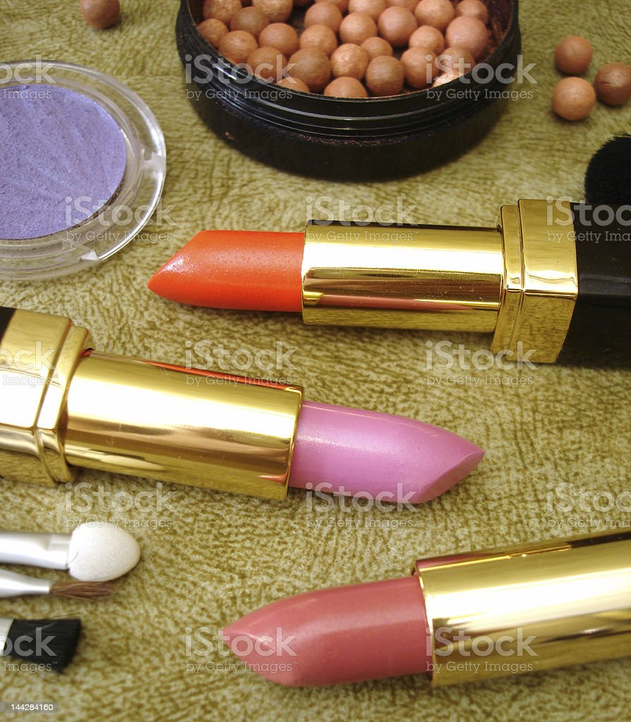 three lipsticks and brown rouge, brushes, eyeshadows royalty-free stock photo