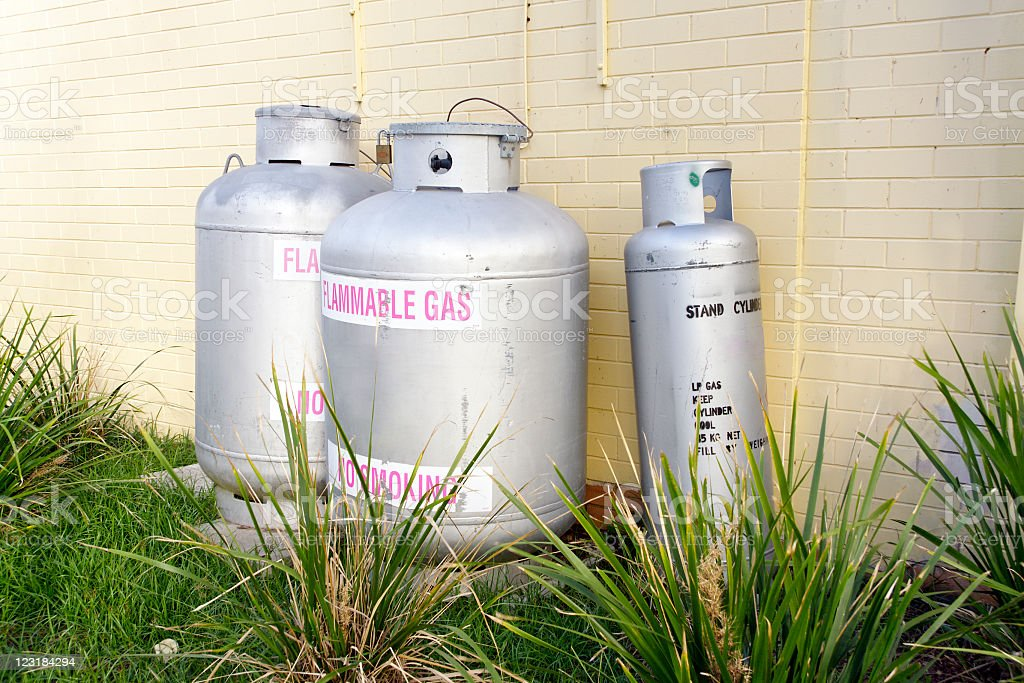 Three Liquefied Petroleum Gas cylinders against a brick wall stock photo