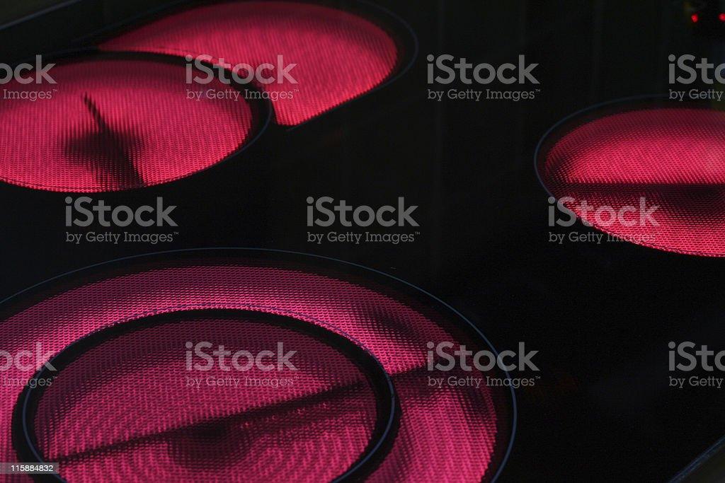 three lit ceramic hobs stock photo