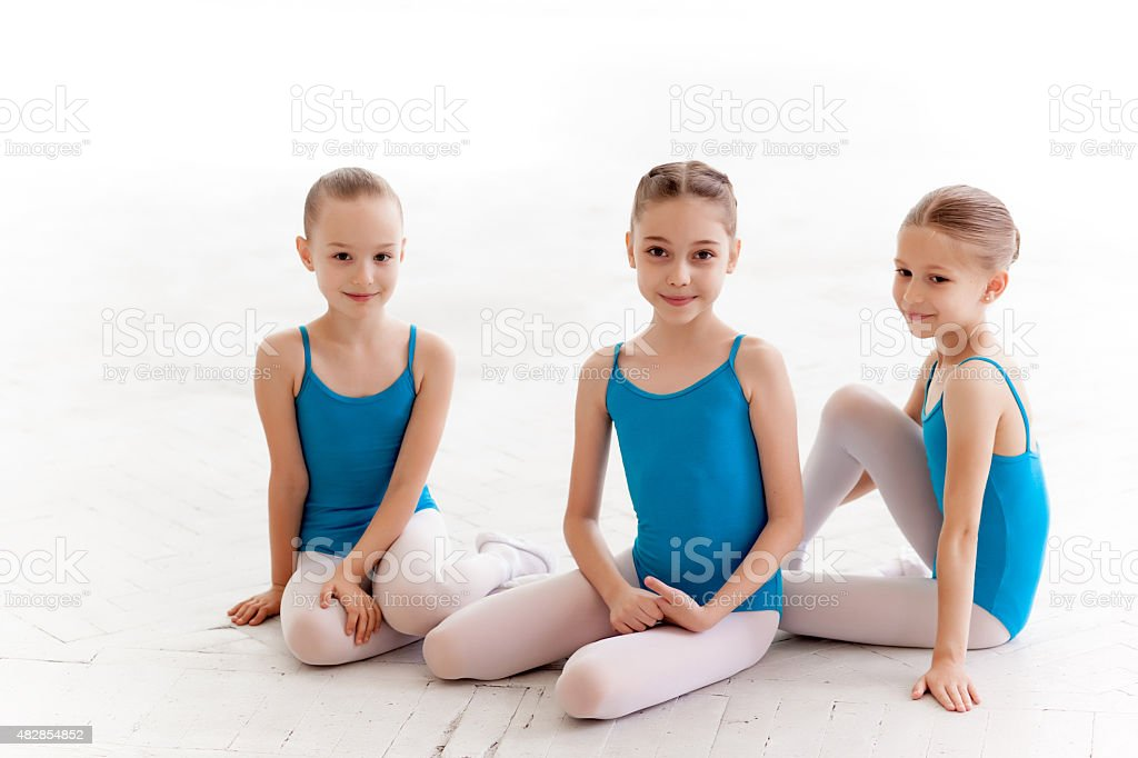 Three little ballet girls sitting and posing together stock photo