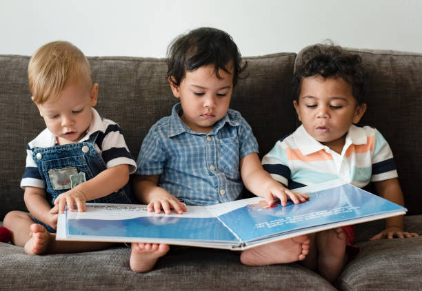 Three little boys reading a book on a sofa stock photo