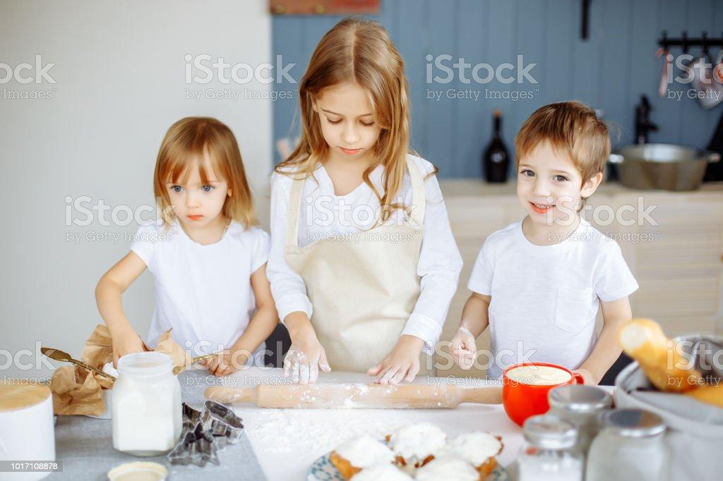 Drie kleine chefkoks genieten in de keuken maken van grote