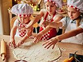 Three little chefs enjoying in the kitchen making big mess. Little girls making bread in the kitchen. Girls at the kitchen. Family housekeeping.