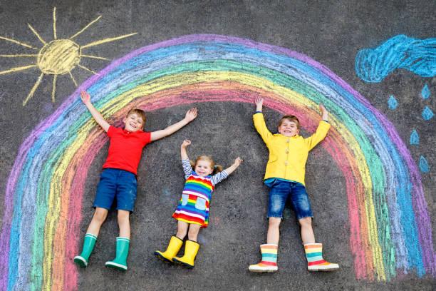 drei kleine Kinder, zwei Schulkinder Jungen und Kleinkind Mädchen Spaß mit regenbogen Bildzeichnung mit bunten Kreide auf Asphalt. Geschwister in Gummistiefeln malen auf dem Boden und spielen zusammen. – Foto