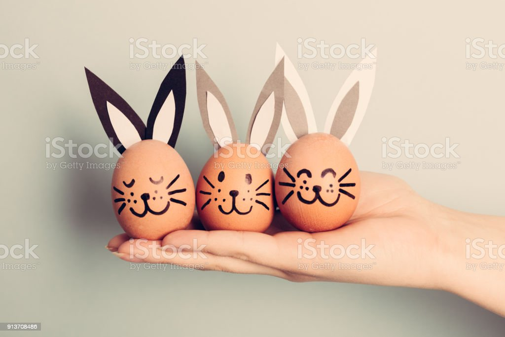 Three little Easter bunnies made from an egg stock photo