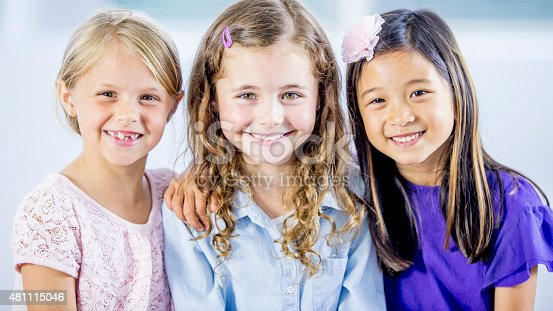 A multi-ethnic group of three little girls sitting together and smiling for the camera.