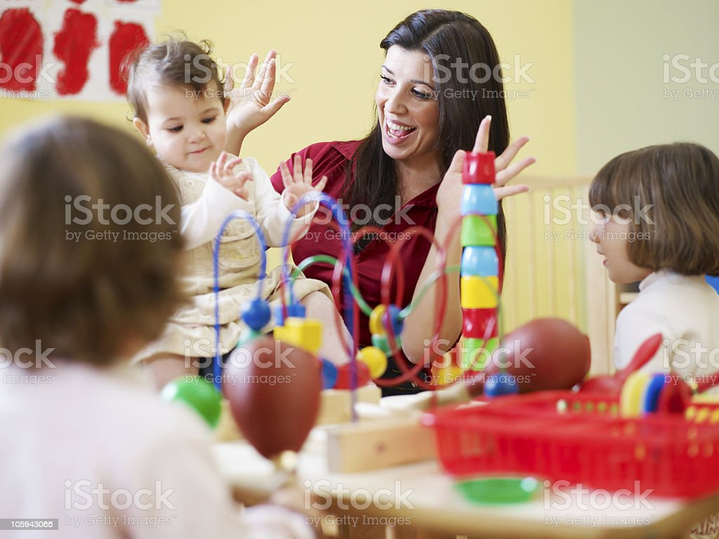 three little girls and female teacher in kindergarten stock photo