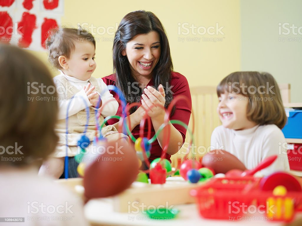 three little girls and female teacher in kindergarten stock photo