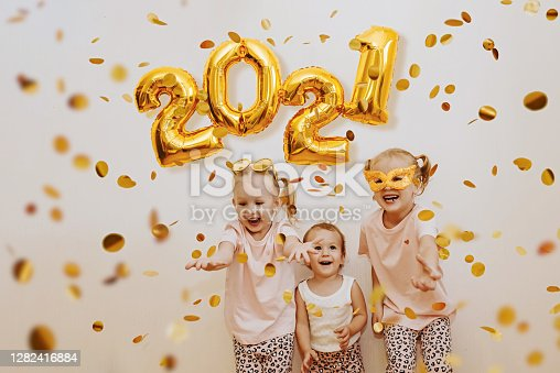 Three little girls are enjoying the flying golden confetti. Celebrating at home 2021. Concept for Christmas and New Year.