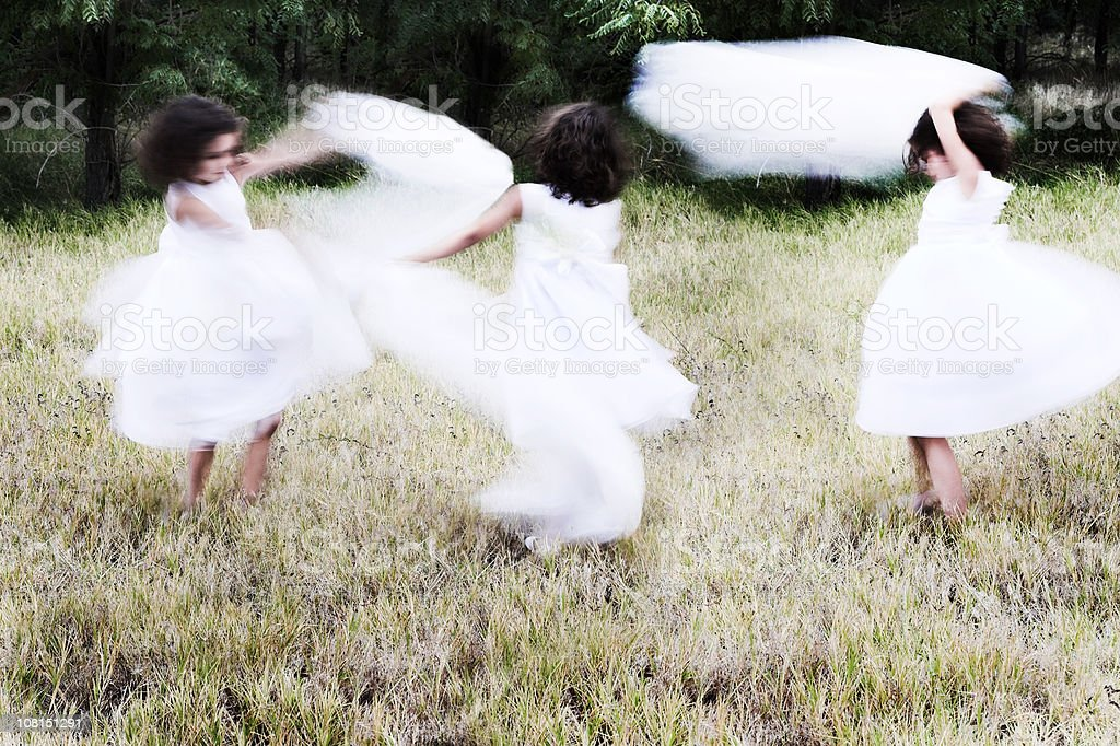 Three Little Girls Dancing In A Meadow royalty-free stock photo