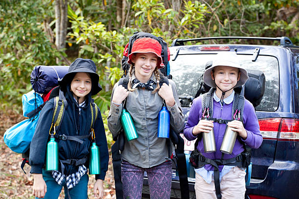 Three Little Girls Hiking Camping with Backpacks Outdoors stock photo