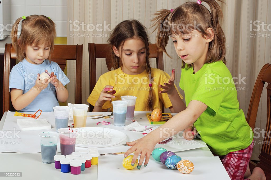 Three little girls (sisters) painting on Easter eggs royalty-free stock photo