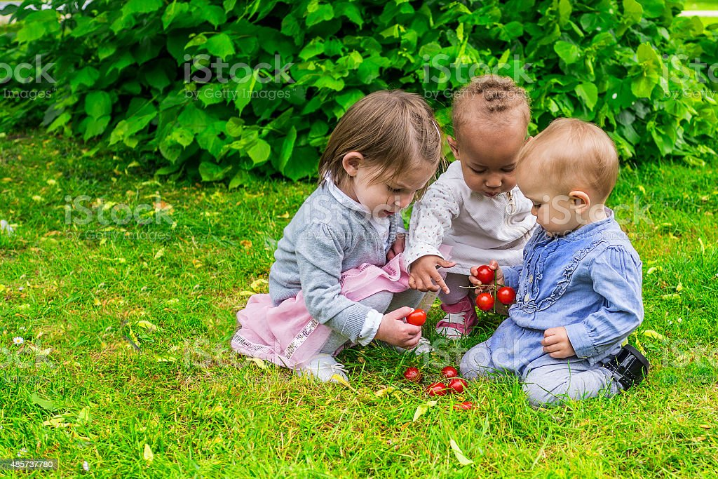 Three little girls playing in the garden stock photo