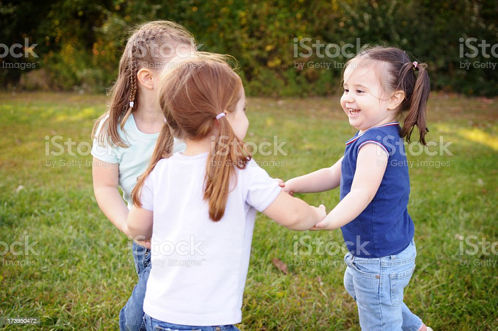 Three Little Girls Playing Ring-Around-the-Rosy royalty-free stock photo