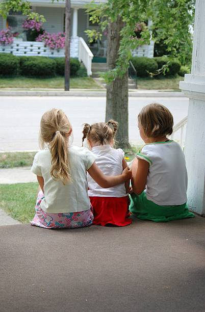 Three Little Girls Sitting On Porch Step stock photo