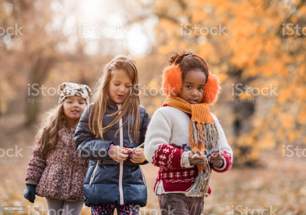 Three little girls walking in a row during autumn day. stock photo