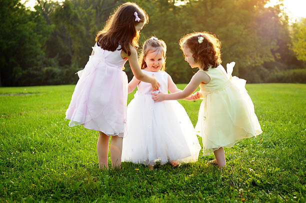 Three Little Girls Wearing Dresses and Playing Outside stock photo