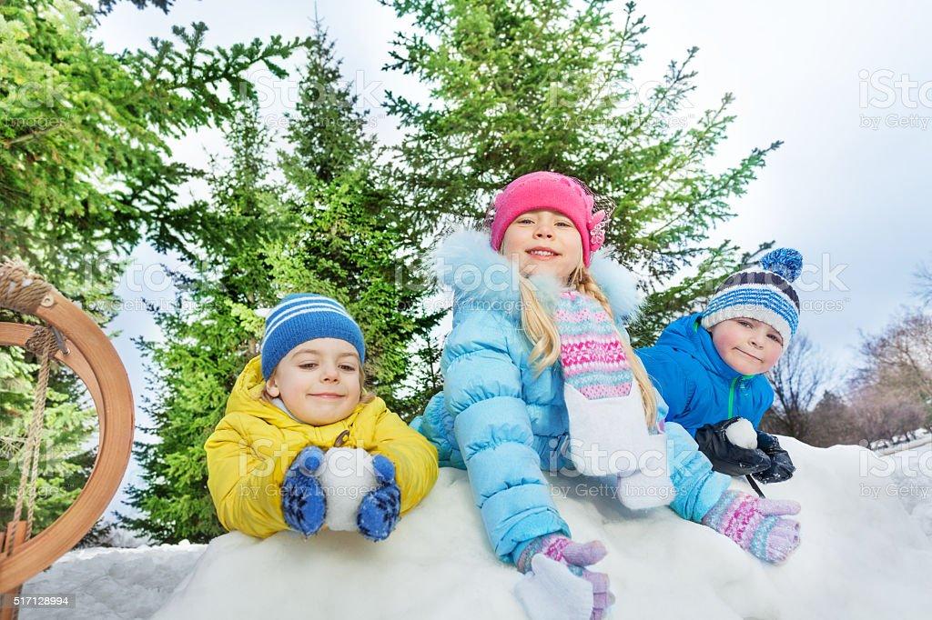 Three little kids play snowball fight stock photo