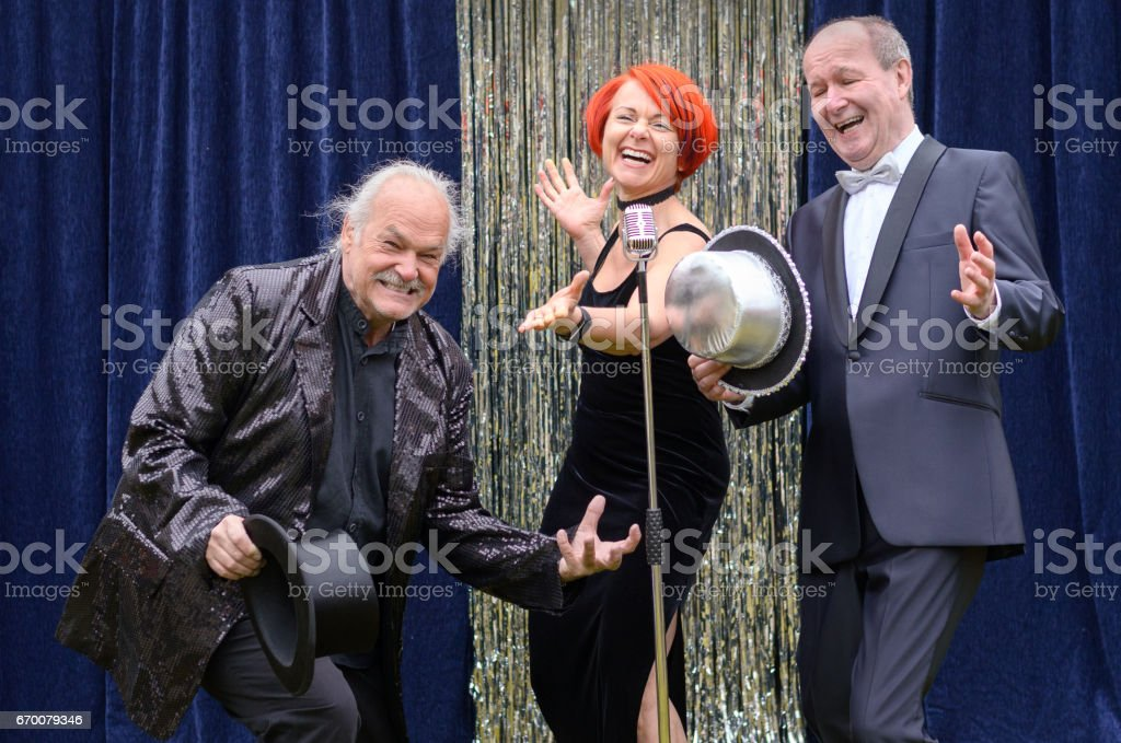 Three lively performers on stage celebrating in front of a microphone...