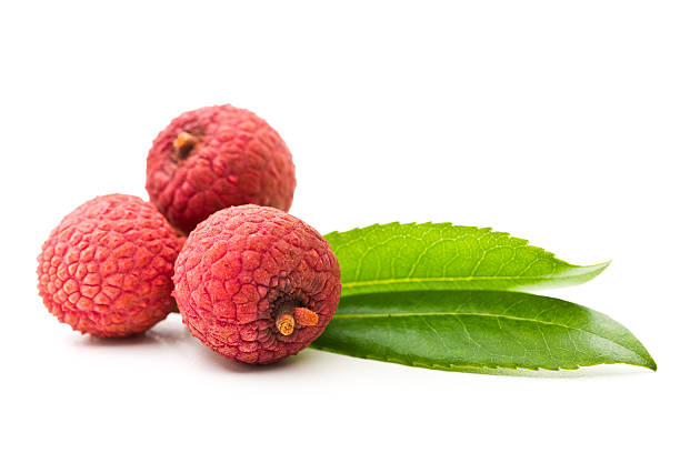 Three lychee berries and leaves on a white background stock photo