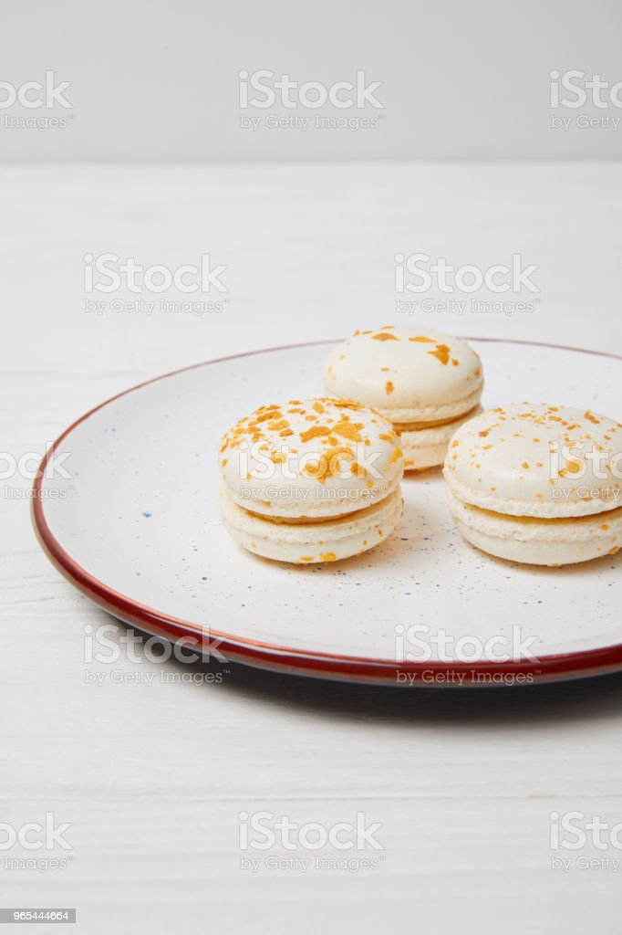 three macarons in plate on white wooden table zbiór zdjęć royalty-free