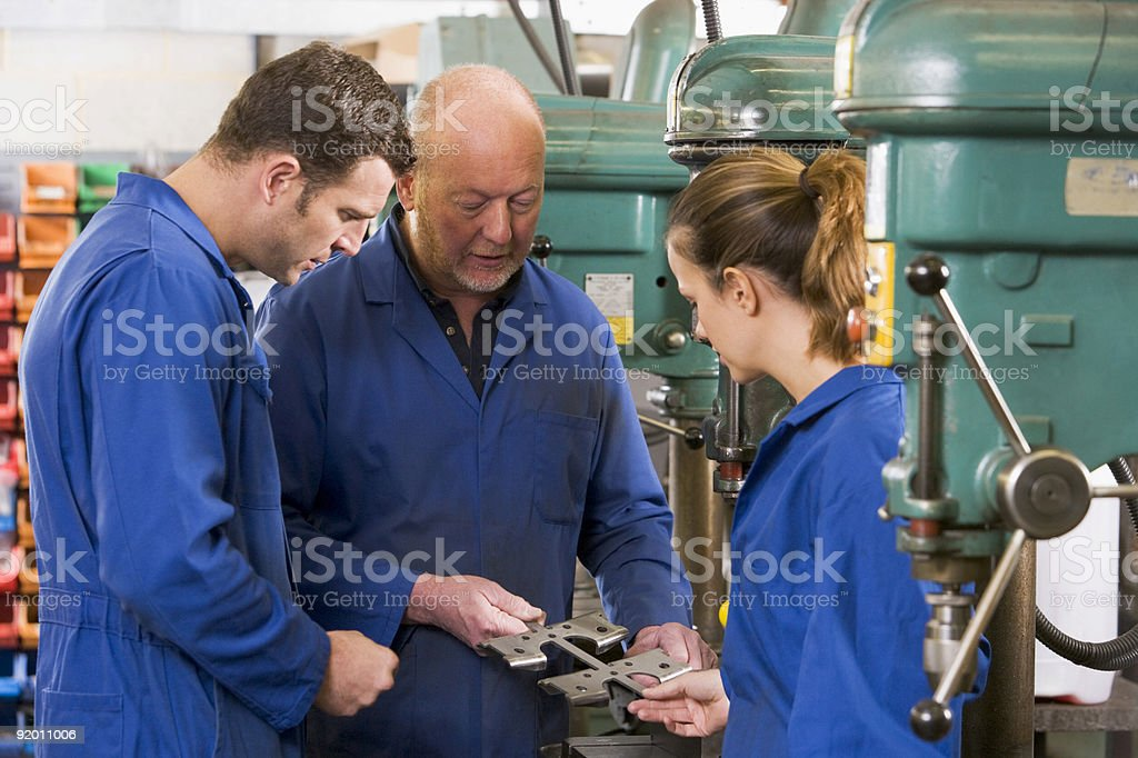 Three machinists in workspace stock photo