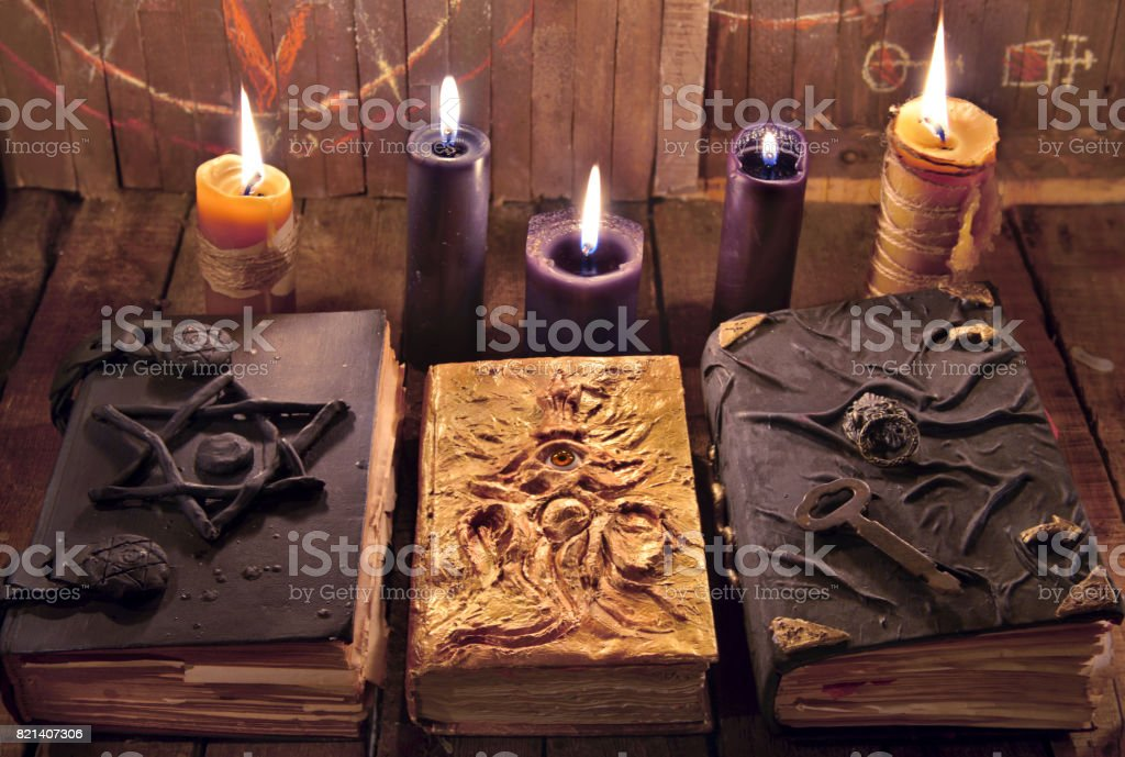 Three magic books with burning candles on planks stock photo