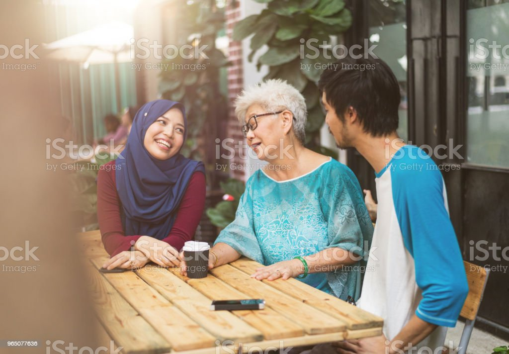 Three malay friends talking to each other royalty-free stock photo