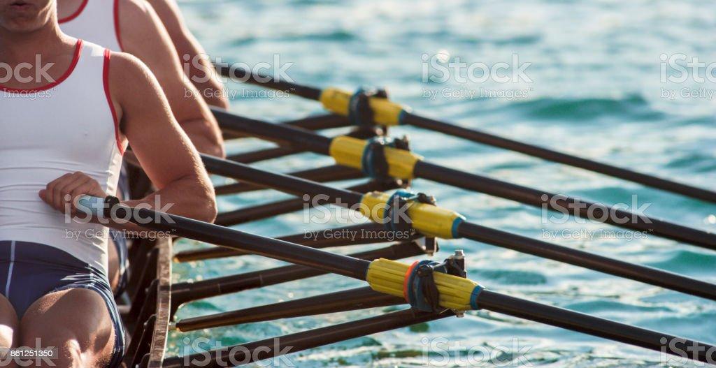 Drei männliche Athleten am späten Nachmittag über See rudern – Foto