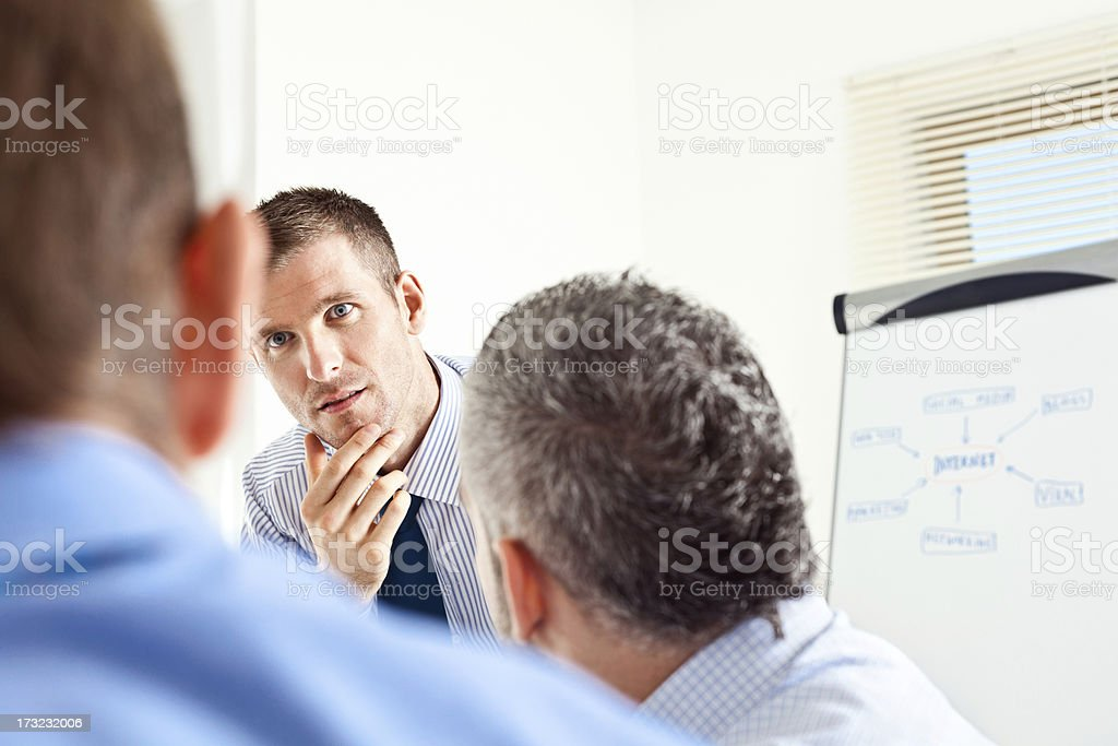 Three male colleagues in business meeting Focus on the businessman listening to his colleague during business meeting. A Helping Hand Stock Photo