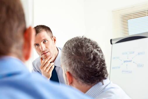Three Male Colleagues In Business Meeting Stock Photo - Download Image Now