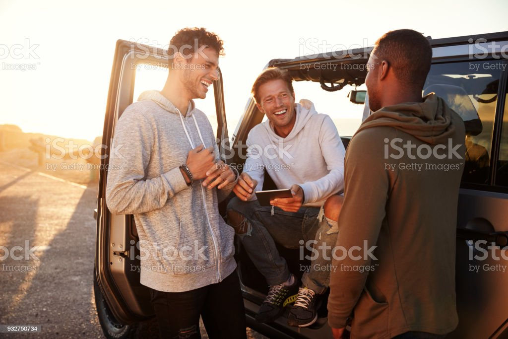 Three male friends on a road trip using a tablet computer royalty-free stock photo