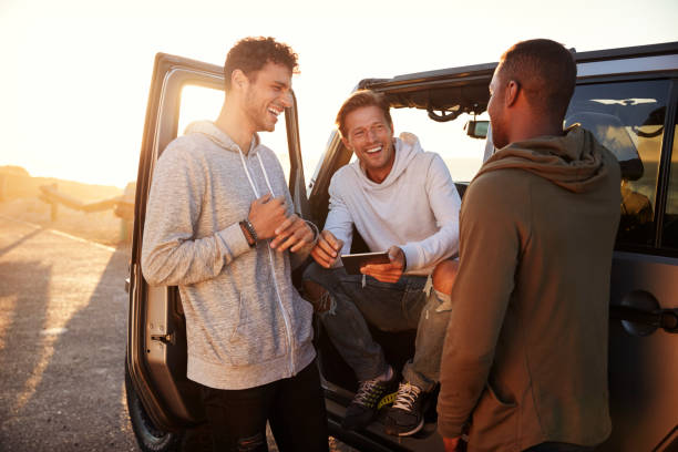 Three male friends on a road trip using a tablet computer stock photo