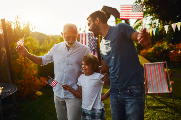 Three Male Generations Celebrating 4th of July Three male generations on picnic in back yard eating hot dog and celebrating 4th of July - Independence Day. family 4th of july photos stock pictures, royalty-free photos & images