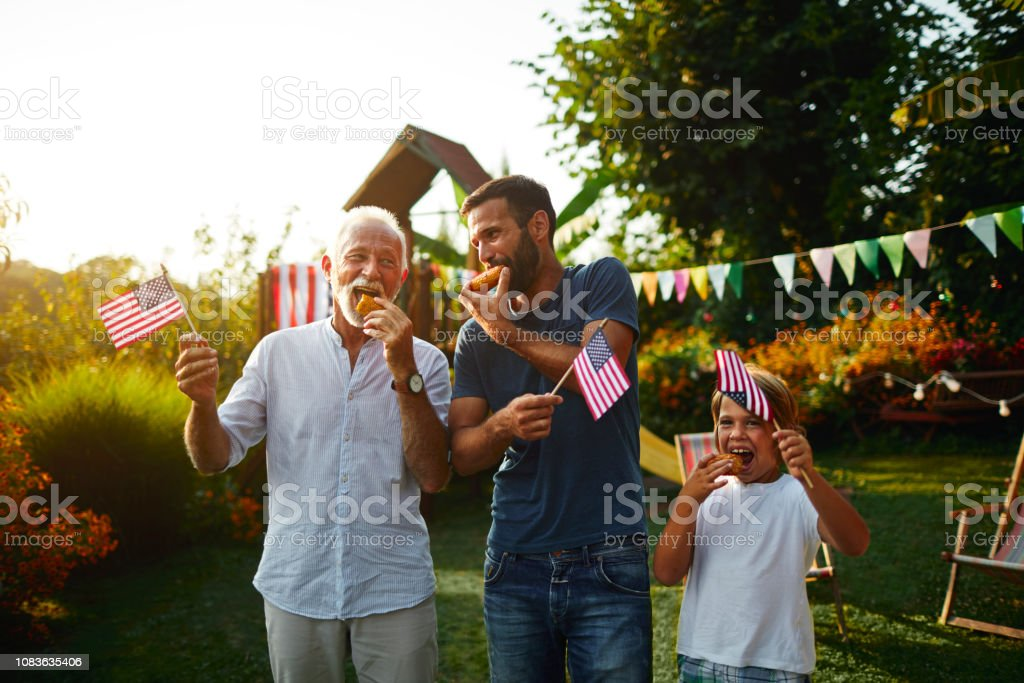 Three Male Generations Celebrating 4th of July Three male generations on picnic in back yard eating hot dog and celebrating 4th of July - Independence Day. 30-39 Years Stock Photo