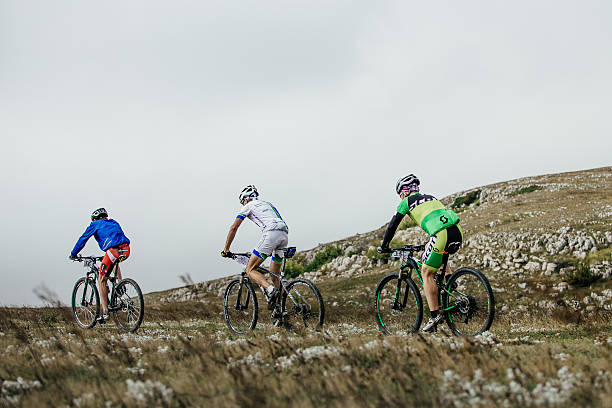 three male riders cyclists mountenbike ride a mountain trail - three roads uphill bildbanksfoton och bilder