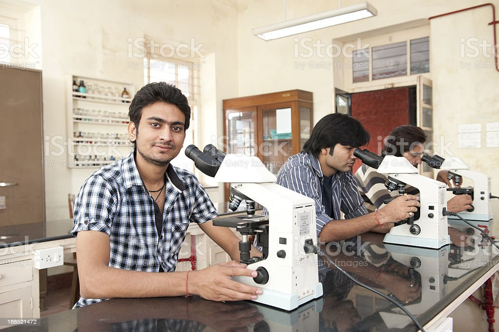 three male students using microscope in a university science laboratory stock photo
