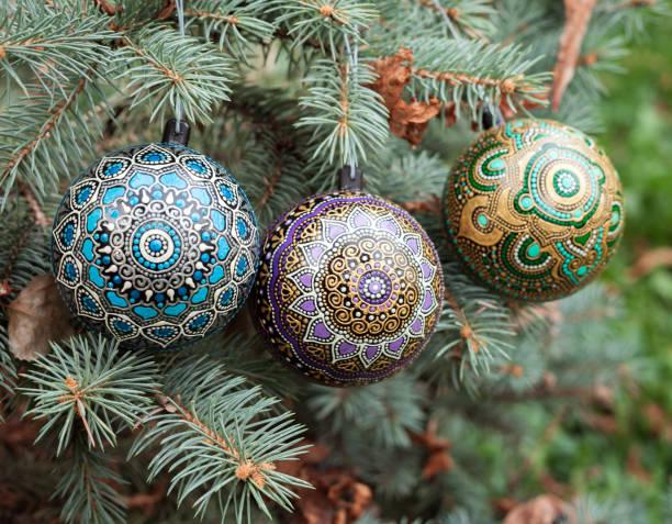 Three mandala christmas balls on pine tree stock photo