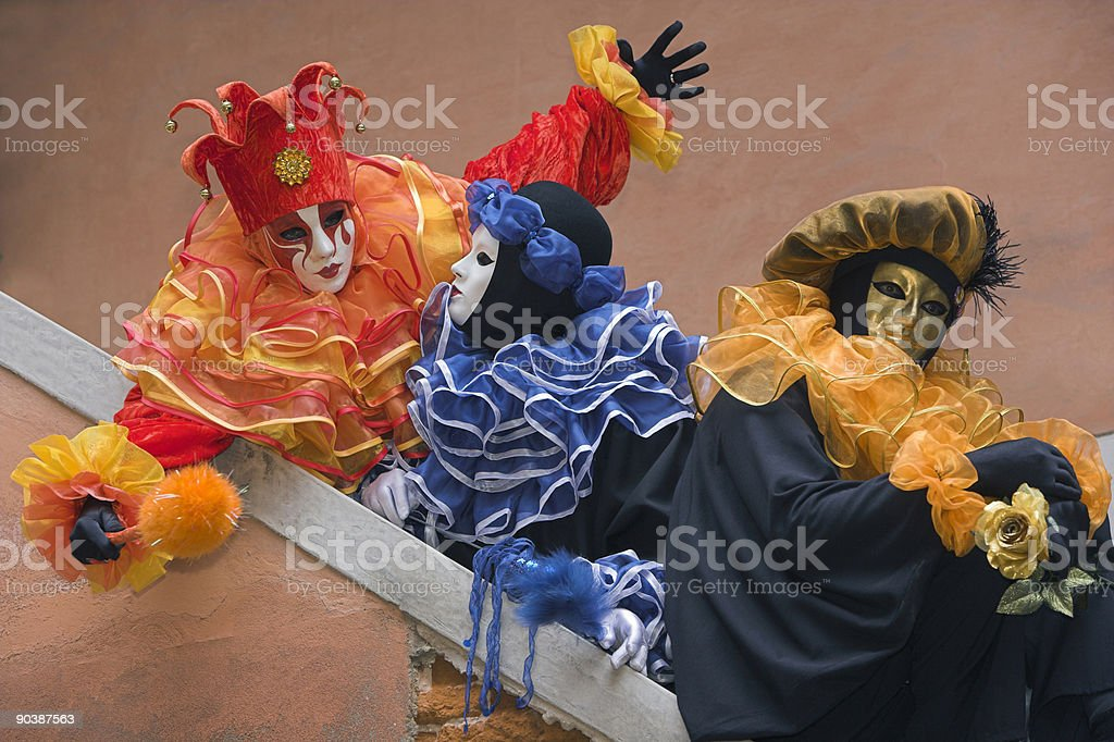 Three masks with colorful costumes at carnival in Venice royalty-free stock photo