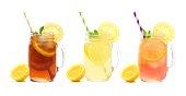 Three mason jars of summer iced tea, lemonade, and pink lemonade drinks isolated on white