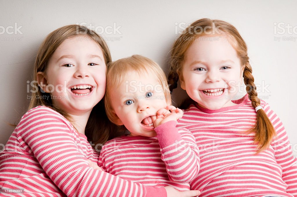 Three Matching Sisters Cuddling and Laughing Together royalty-free stock photo