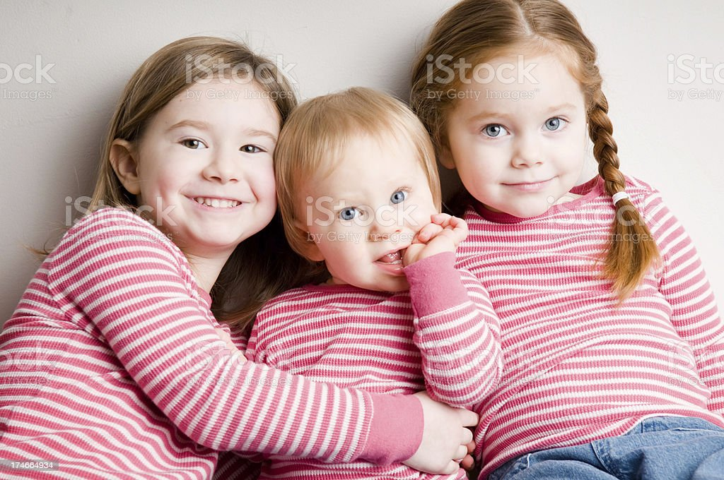 Three Matching Sisters Cuddling Together royalty-free stock photo
