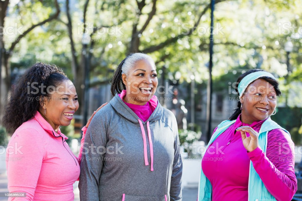 Three mature African-American women wearing sports clothing, standing...