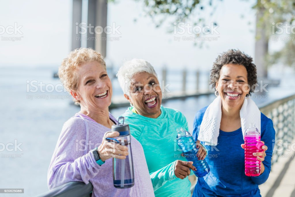 Three mature and senior women exercising on waterfront stock photo