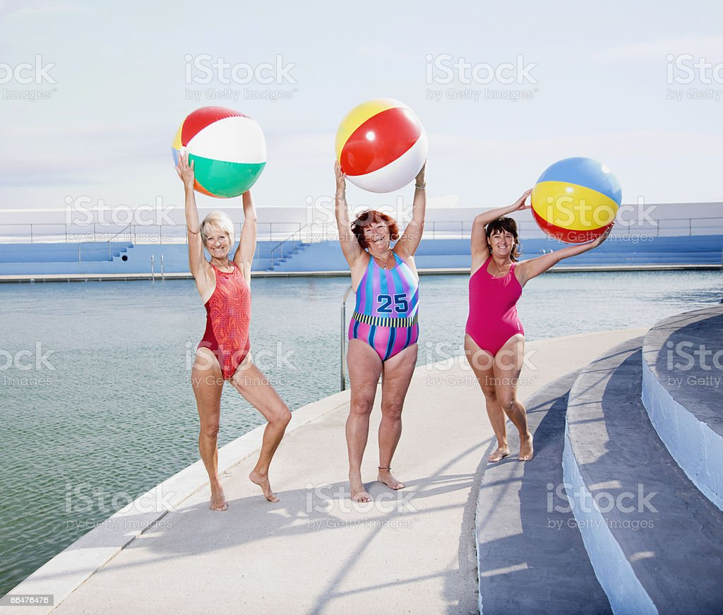 Three mature ladies posing at the pool royalty-free stock photo