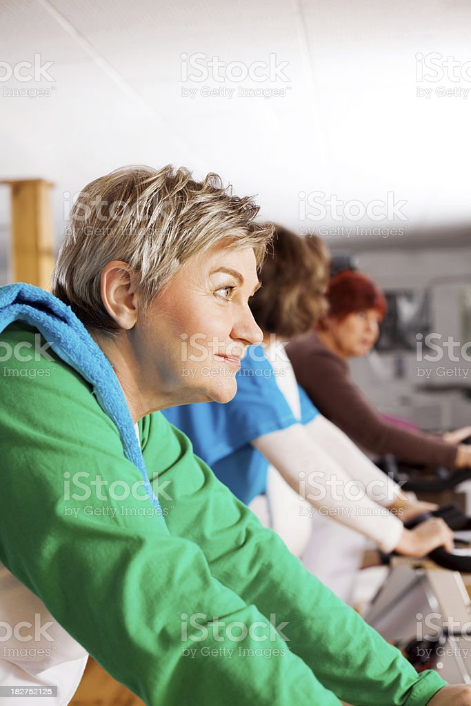 Three Mature Women Cycling At the Gym royalty-free stock photo