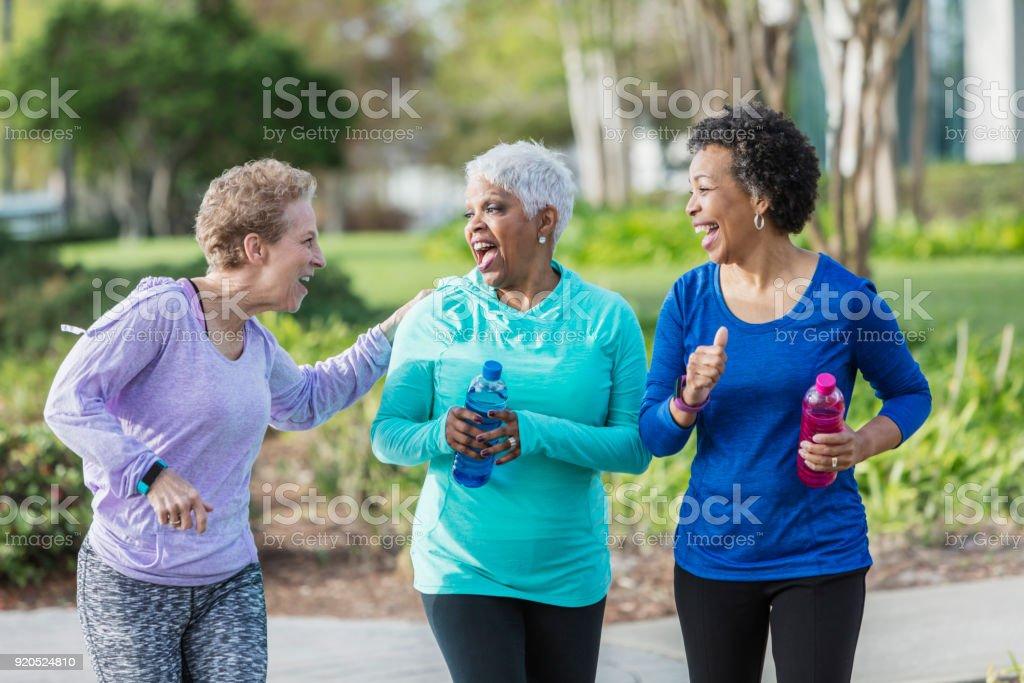 Three mature women exercising in park, walking, talking stock photo