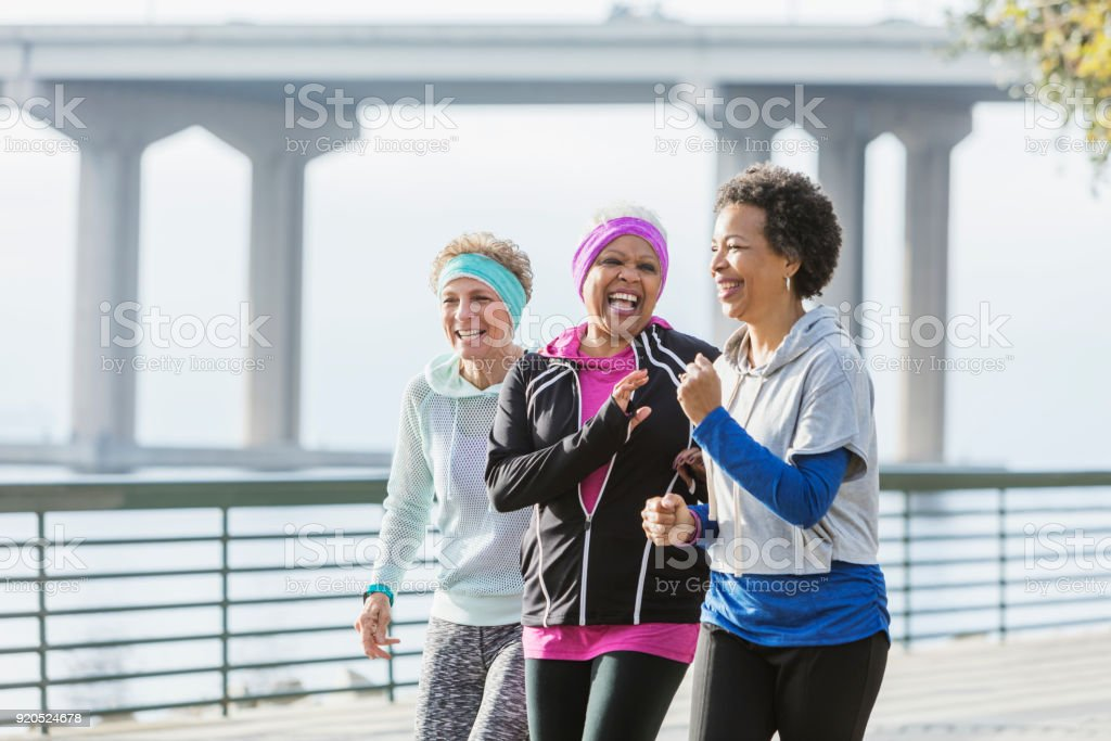 Three mature women power walking together on waterfront stock photo