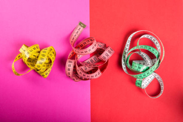 Three measuring tape on red and pink background stock photo