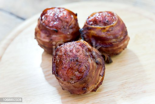 istock Three meatballs and covered with bacon on cutting board 1068852328